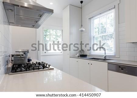 New renovated crisp white galley style kitchen in Australian apartment - stock photo