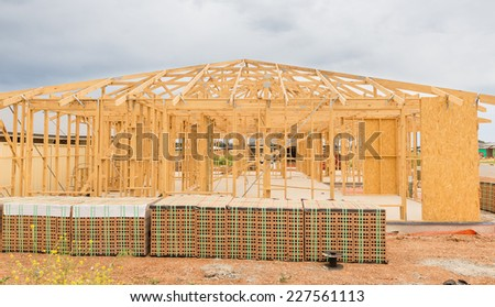 New residential construction home framing against a cloudy sky - stock photo