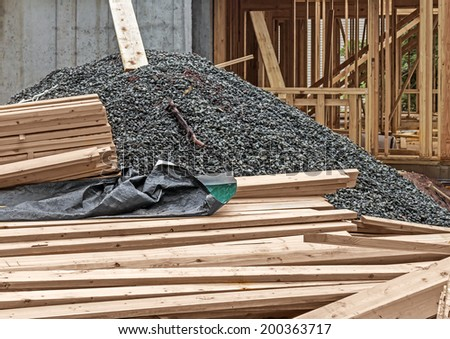 New residential construction, unfinished house. Stack of wood planks partly covered with a wet tarp, pile of gravel and small rocks. Wood frame house blurred in background.  - stock photo