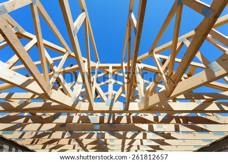 New residential wooden construction home framing against a blue sky - stock photo