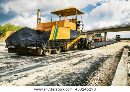 New Road - Pavement machine laying fresh asphalt or bitumen on top of the gravel base during highway construction - stock photo