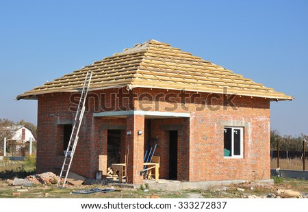 New Roof Membrane Coverings Wooden Construction Home Framing with Roof Rafters and Metal Ladder Outdoor against a Blue Sky. Roofing Construction Exterior with Red Brick house Wall Facade. - stock photo