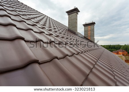 New roof with natural red tile and chimney - stock photo