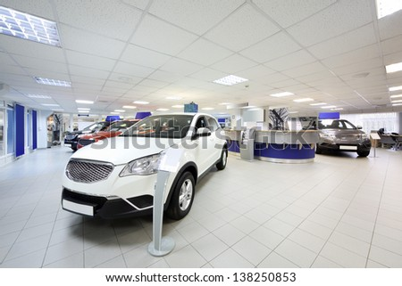 New shining beautiful cars stand near desk reception in car shop. - stock photo