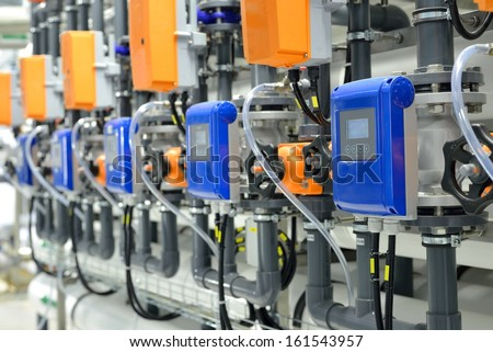 new shiny pipes and colorful equipment in industrial boiler room - stock photo