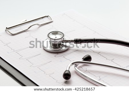 new stethoscope on a white background with cardiogram close up - stock photo