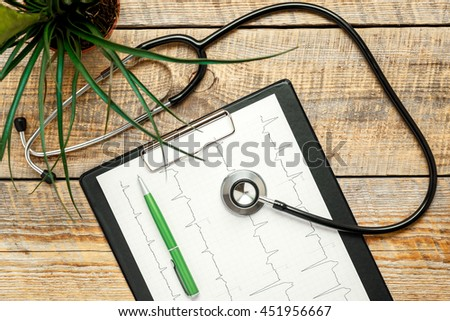 new stethoscope on wooden table with cardiogram - stock photo