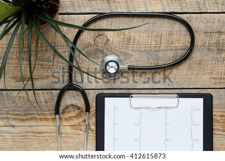 new stethoscope on wooden table with cardiogram isolated - stock photo