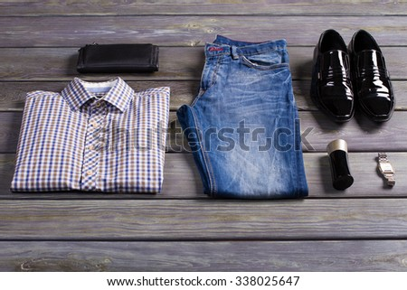 New stylish men's clothing on store shelf. - stock photo