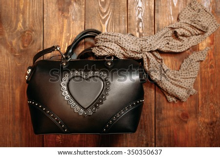 New stylish women's leather bag decorated with a scarf. View from above. One bag on a wooden background - stock photo