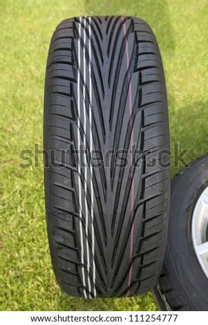 new tire tread on car wheel - stock photo