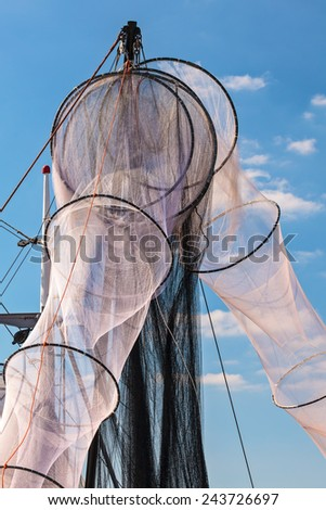 New unused hanging fishing nets in Holland against a blue sky - stock photo