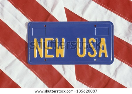 New USA license plate on stripes of American flag - stock photo