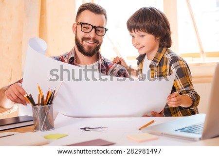 New vision of old things.Cheerful young man and his son looking through blueprint while sitting at working place  - stock photo