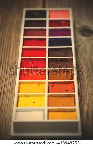 new watercolor paint-box on old textured surface of ancient table. close up. handmade. shallow depth of field. instagram image filter retro style - stock photo