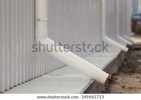 New white rain gutter on a building with white metal sheet  - stock photo