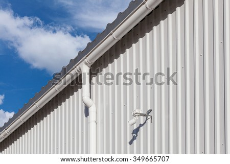 New white rain gutter on a building with white metal sheet and guard camera against blue sky - stock photo
