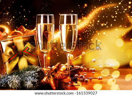 New Year and Christmas Celebration. Two Champagne Glasses and Gifts over Golden Blinking Holiday Background  - stock photo