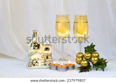 New Year and Christmas still life with glasses of sparkling wine, candles and ceramic house-candlestick, silver-yellow tones - stock photo