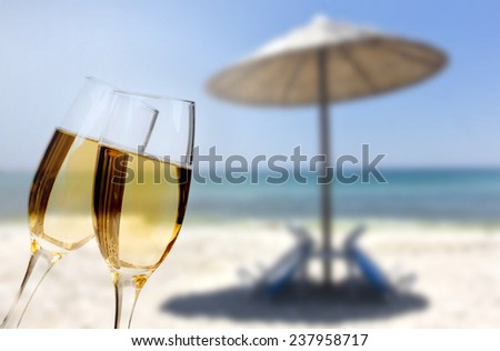 New Year at the beach - Glasses of champagne on the beach against the sky and blue sea - stock photo