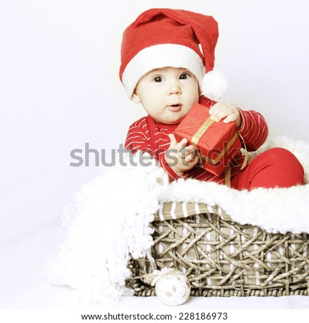 New Year baby wear santa hat and Xmas gift in her hand - stock photo