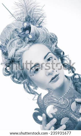 New Year Carnival.  Young woman in eighteenth century image posing with mask. - stock photo