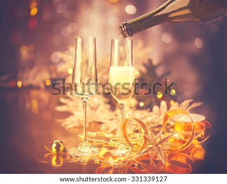 New Year celebration with champagne. Champagne Christmas and New Year celebration. New Year holiday decorated table. Two Champagne Glasses, vintage toned - stock photo