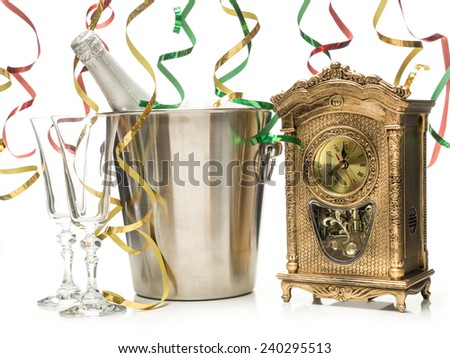New Year champagne bottle in cooler, two champagne glasses and table clock showing midnight shot on white - stock photo
