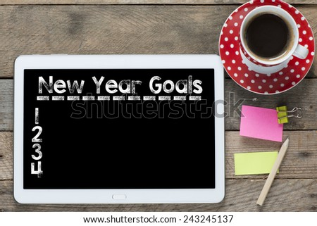 New year goals and computer. Tablet computer with stickers,cup of coffee and New year goals on the wooden table - stock photo