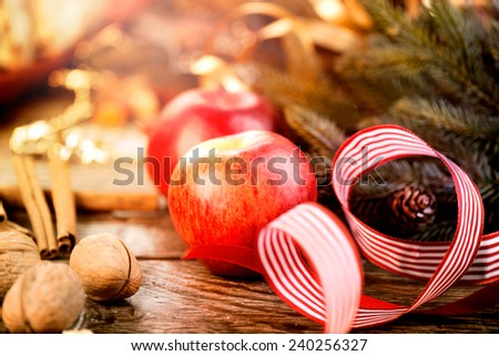 New Year holiday table setting, decorated with garlands, baubles, walnuts, hazelnuts, cinnamon sticks. Warm colors toned. Traditional Christmas sweets food. Vintage style toned image - stock photo