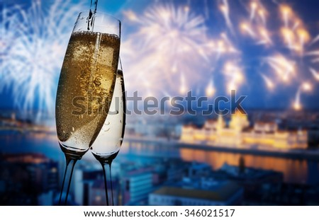 New Year in Budapest - Champagne glasses and Budapest parliament with fireworks in the background - stock photo