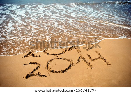 New Year 2014 is coming concept - inscription 2013 and 2014 on a beach sand, the wave is covering digits 2013 - stock photo