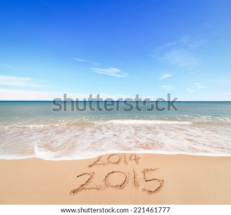 New Year 2015 is coming concept - inscription 2014 and 2015 on a beach sand, the wave is covering digits 2014 - stock photo