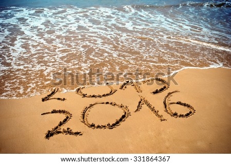 New Year 2016 is coming concept - inscription 2015 and 2016 on a beach sand, the wave is covering digits 2015 - stock photo