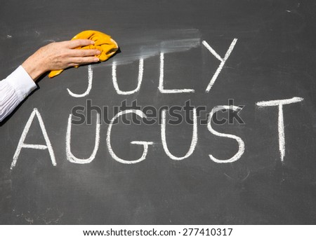 New Year is coming concept - inscription July and August on a school blackboard, with the words July being erased by the teacher. - stock photo