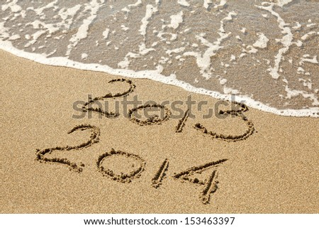 New Year 2014 is coming. Inscription 2013 and 2014 on a beach sand, the wave is covering digits 2013.  - stock photo