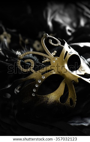 New Year party masquerade mask against a dark seductive background. Concept image for erotic liaisons and mysterious seduction. Selective focus with creative lighting. - stock photo