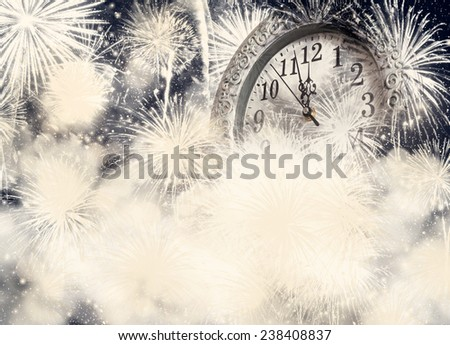 New Year's at midnight - old clock on bokeh background of holiday lights and fireworks - stock photo