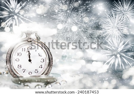 New Year's at midnight - Old clock with fireworks and holiday lights - stock photo