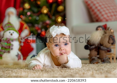 New Year's Concept. Adorable little girl near a Christmas tree with presents. with finger in the mouth new year - stock photo