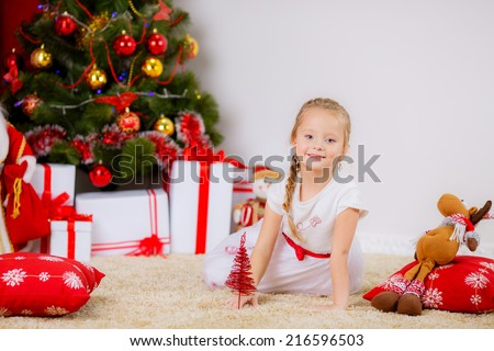 New Year's Concert. Adorable girl near a Christmas tree with presents. new year - stock photo