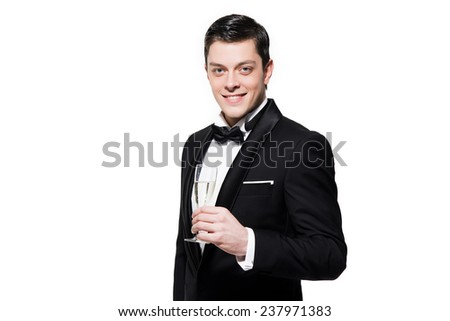 New year's eve fashion man wearing black dinner jacket. Holding glass of champagne. Isolated against white. - stock photo