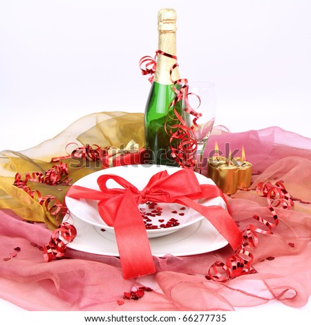New Year's or Valentine's setting - a plate decorated with ribbon and heart shaped confetti, a bottle of champagne, a glass, candles, a gift - stock photo