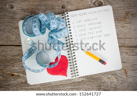 New year's resolutions written on a notepad with a measure tape and heart - stock photo