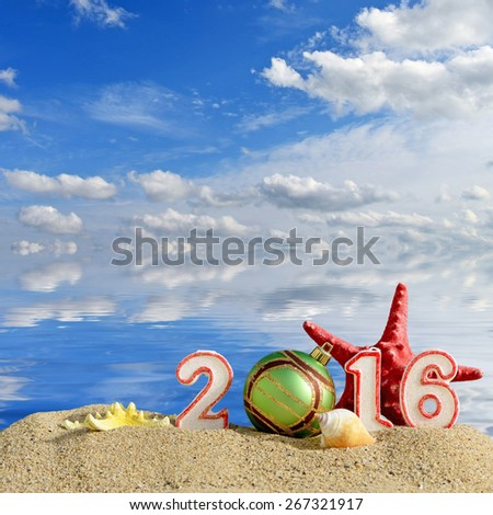 New year 2016 sign on a beach sand with seashells, starfish and christmas ball - stock photo