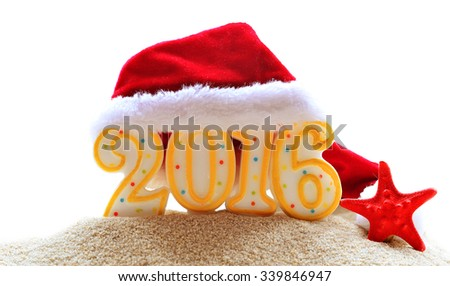 New year 2016 sign with  Santa Claus hat on sand - stock photo