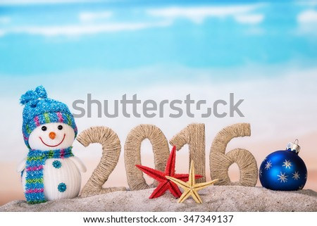 New year sign with starfishes on sandy beach and snowman - stock photo