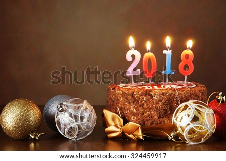New Year 2018 still life. Chocolate cake and decorative tree balls with burning candles on brown background - stock photo