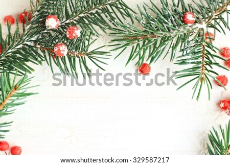New Year wintry snowy decoration: new year branches and berries natural, white wooden backdrop, framed DIY christmas congratulation card.  - stock photo