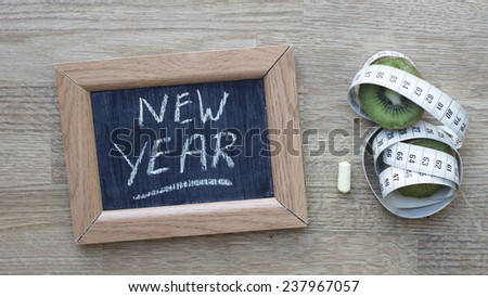 New year written on a chalkboard next to a kiwi an inches - stock photo